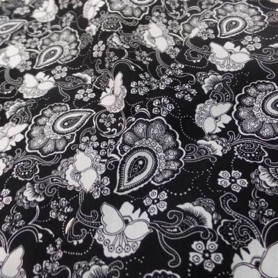 Coton popeline noire imprime fleurs ton blanc