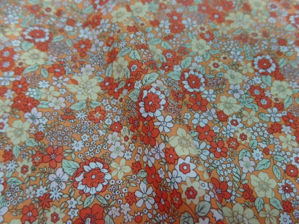 Coton popeline orange imprime liberty motifs petite fleurs